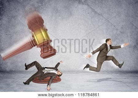 Inscribed gavel hitting businessman