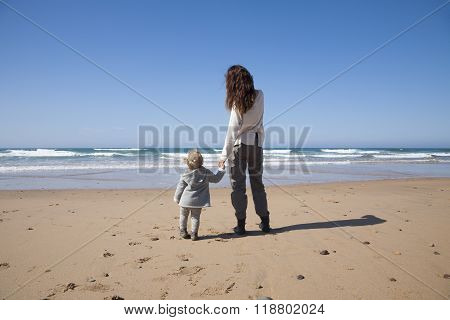 Baby And Mother Holding Hands In Beach
