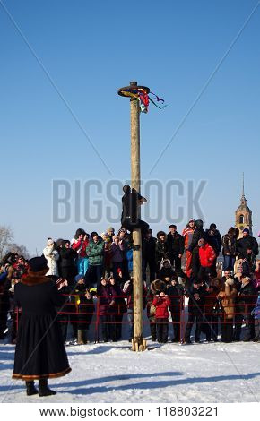 Suzdal, Russia - February 21, 2015: Shrovetide In Russia. Man Climbing The Pole For Prize During