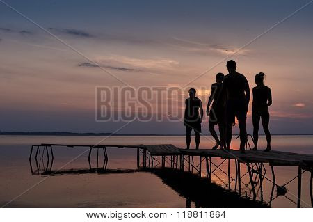 Three Men And One Girl To Go Swimming At Sunset