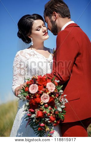 Bride and groom, lovely couple outdoor, wedding bridal bouquet with red flowers. Blue sky, green gra