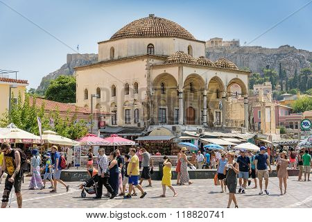 Old church and tourists walking at Monastiraki square of Athens
