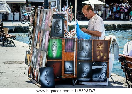 Street seller trading hand made pictures at harbour of Chania town