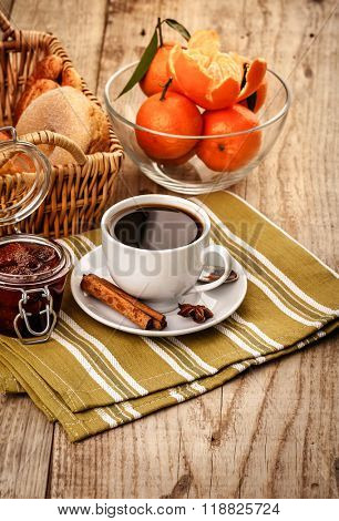 Breakfast with coffee and fruits for good morning. Tangerines and sweet jam on wooden board in rustic style