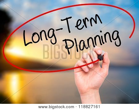 Man Hand Writing  Long-term Planning With Black Marker On Visual Screen