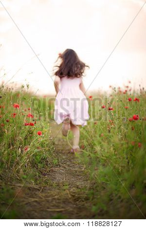 Little girl running away in a field of poppies