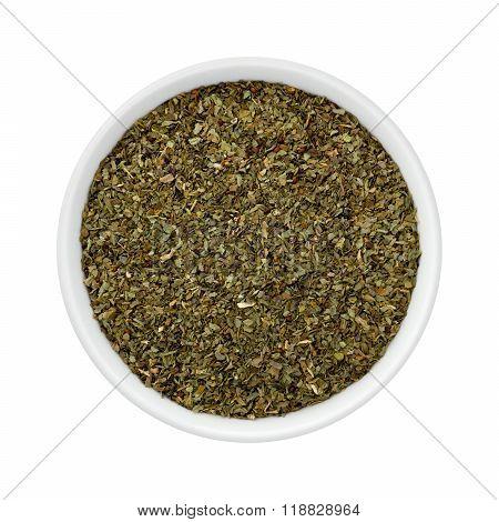 Dried Basil Flakes In A Ceramic Bowl