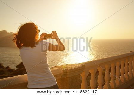 Girl photographing sunset with her phone