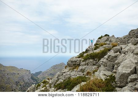 Young man standing on cliff with hands raised on top of mountain at Sa Colobra, Majorca, Spain. Happy man winner on top of mountain.