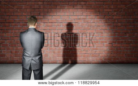 Businessman standing in spotlight front of brick wall