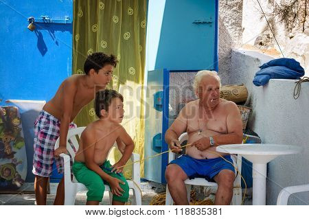 Old man man with rope in hands sits on chair and two his grandsons are near him