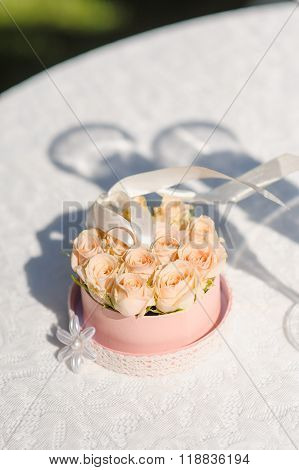 Wedding decoration concept. Two golden wedding rings stand in roses
