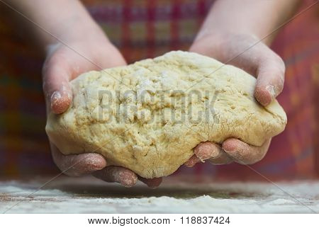 Kneading dough. Close-up of female hands in flour kneading dough