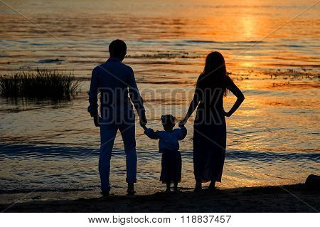 silhouettes parents and child on the background of sunset