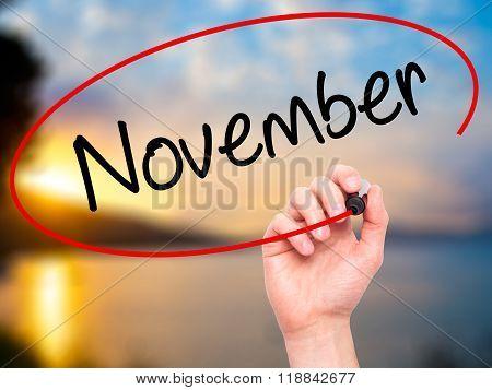 Man Hand Writing November With Black Marker On Visual Screen