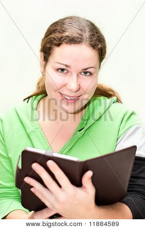 Beautiful Girl Holding Ebook In Hands And Looking At Camera