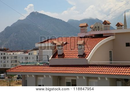 Tile-roofed House In The Sun On A Background Of Mountains In The Summer