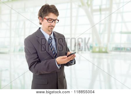 young business man looking worried to his phone, at the office