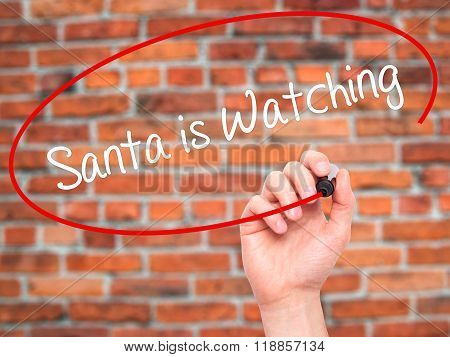 Man Hand Writing Santa Is Watching With Black Marker On Visual Screen