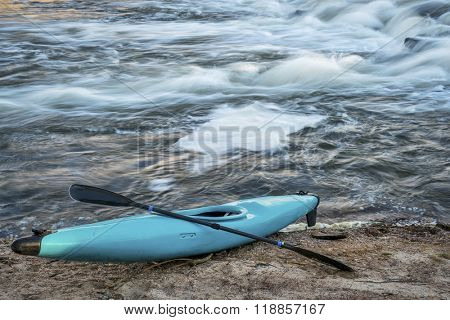 blue plastic white water kayak with a paddle on a river shore with a rapid in background