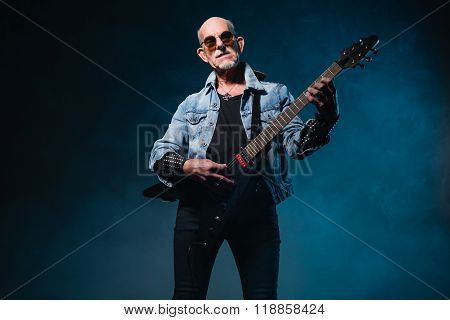 Bald Heavy Metal Senior Man With Electric Flying-v Guitar In Front Of Dark Blue Background.