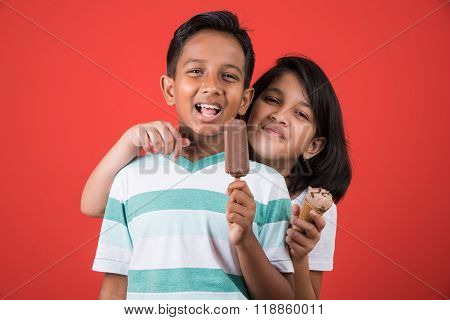 two happy indian kids and ice cream, two asian kids enjoying ice cream or cone or chocolate candy, g