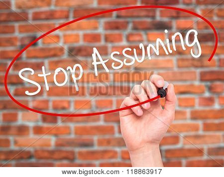Man Hand Writing Stop Assuming With Black Marker On Visual Screen