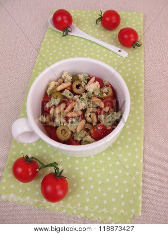 Crumble mug cake with tomatoes, olives, cheese crumbles and pine nuts