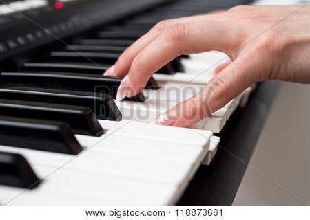 Woman hand playing a MIDI controller keyboard synthesizer close up