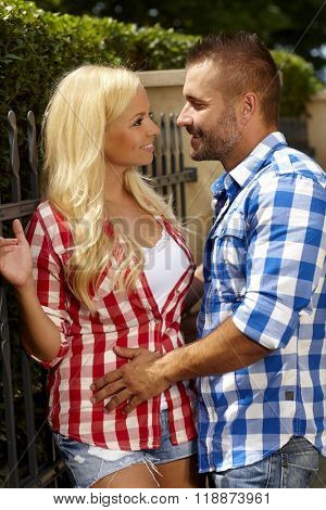 Attractive young blonde casual woman and stubbly handsome man outdoor, leaning against fence, smiling.