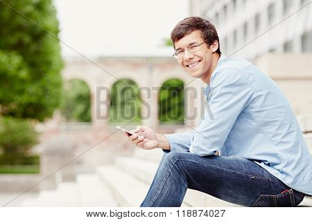 Young hispanic man wearing glasses, blue shirt and jeans, sitting on stairs outdoors, holding mobile phone in his hand and smiling - communication concept