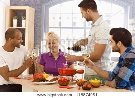 Young friends having fun together, drinking and eating at home, smiling, clinking glasses.