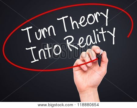 Man Hand Writing Turn Theory Into Reality With Black Marker On Visual Screen