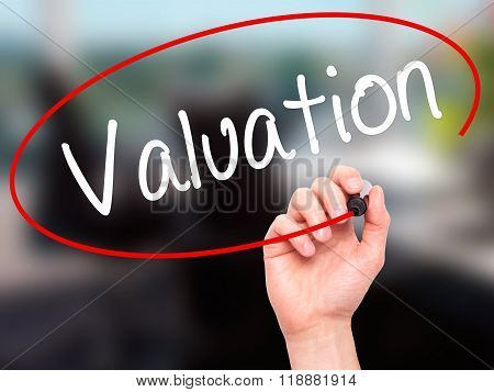 Man Hand Writing Valuation With Black Marker On Visual Screen