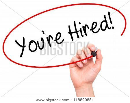 Man Hand Writing You're Hired! With Black Marker On Visual Screen