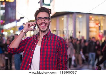 Man making a phone call on Times Square, New York, at night.