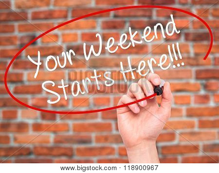 Man Hand Writing Your Weekend Starts Here!!! With Black Marker On Visual Screen