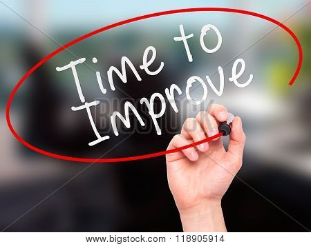 Man Hand Writing Time To Improve With Marker On Transparent Wipe Board Isolated On Office