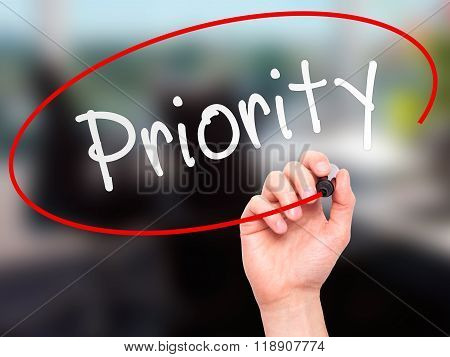 Man Hand Writing Priority With Marker On Transparent Wipe Board