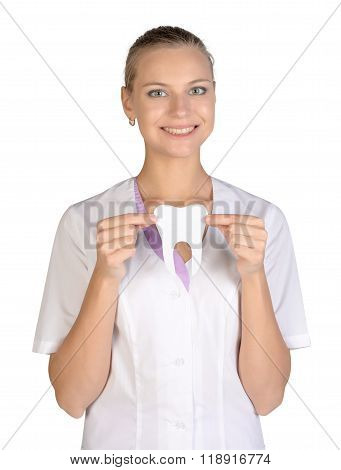 Smiling woman dentist holding a white paper tooth