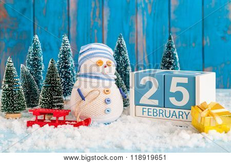 February 25th. Cube calendar for february 25 on wooden surface with snowman, sled, snow and fir