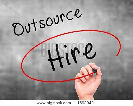 Man Hand Writing And Choosing To Hire Instead Of Outsource With Black Marker On Visual Screen