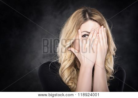 Woman peeping through her fingers.