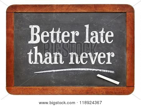 Better late than never proverb - white chalk text on a vintage slate blackboard