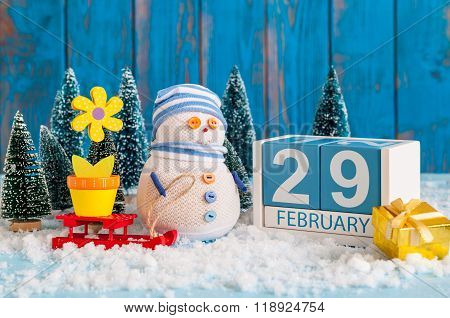 February 29th. Cube calendar for february 29 on wooden surface with snowman, sled, snow, fir and spr