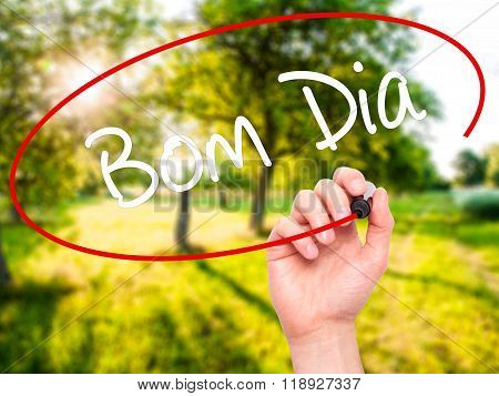 Man Hand Writing bom Dia (in Portuguese - Good Morning)  With Black Marker On Visual Scr