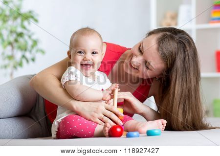 cute mother and baby play indoor at home
