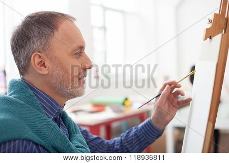 Cheerful old artist is painting in his studio