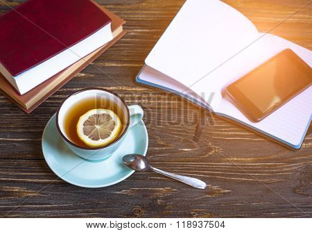 Hot tea with lemon, notebook and phone on wood background - seasonal relax concept