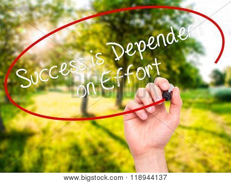 Man Hand Writing Success Is Dependent On Effort With Black Marker On Visual Screen
